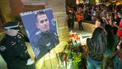 Family, friends and fellow officers leave candles,