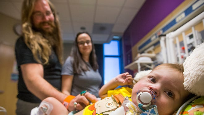 Henry Bailey, 19 months, has a failing heart and is waiting for a transplant to survive.  His parents, Elias Bailey, left, and Samantha Bailey, visit the baby in his room at Phoenix Children's Hospital, Thursday, May 11, 2017.
