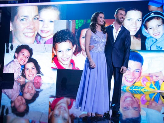 "In this April 10, 2017 photo released by ABC, former Olympic figure skater Nancy Kerrigan appears with her dance partner Artem Chigvintsev as photos of Kerrigan with her children appear on a screen during the competition series, ""Dancing with the Stars.""  Kerrigan opened up about her personal struggles after having six miscarriages in an eight-year span."