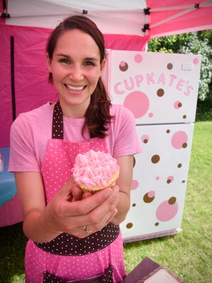 Katie Kirkeby holds one of her cupcakes at her stand Cupkate's Saturday, June 11, at the Sartell SummerFest Maker's Fair.