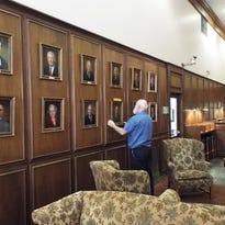 Tallahassee Democrat building services technician Alton Lawrence levels portraits he hung of past Democrat leaders. The portraits are on display to visitors to the lobby of the Democrat at 277 N. Magnolia Drive.