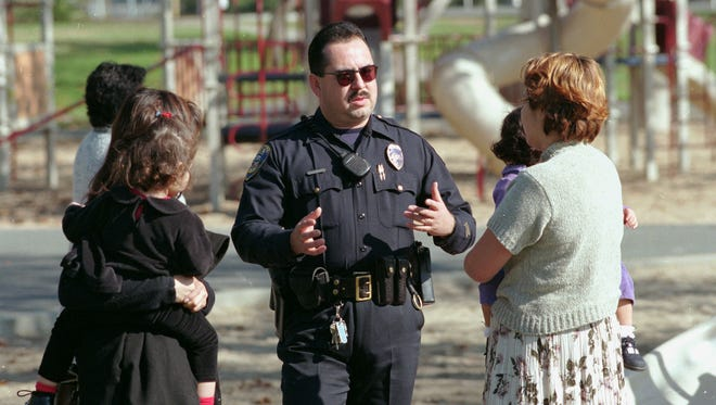 A community police officer talks with mothers and their children, 1998.