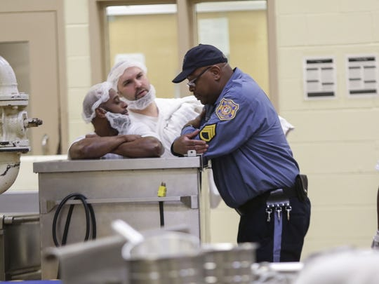 (left to right)Inmates Dashawn Brooks and Neil Carrier talk with correctional officer Steve Burton while working in the kitchen at Jame T. Vaughn Correctional Center.