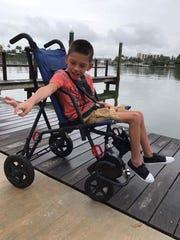 Kaden Cortello, 9, of Navarre, uses a beach wheelchair