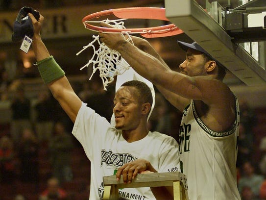 Morris Peterson, left, waves to the crown as teammate