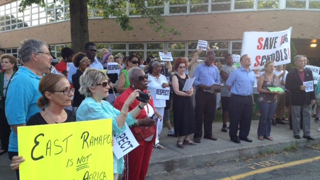 East Ramapo parents rally prior to a school board meeting July 8, 2013, calling for the ouster of school board attorney Christopher Kirby after his profanity-laden blow-up at parent activists on school property.