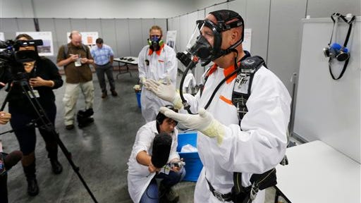 Bob Wilkinson, right, an environmental safety manager for the contractor Washington River Protection Solutions, demonstrates protective clothing and a scuba-type tank-and-mask breathing apparatus used by workers in areas with potential exposure to possibly harmful vapors during a media tour of the Hanford Nuclear Reservation July 9, 2014.
