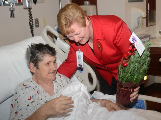 ANI Cabrini Christmas Trees St. Frances Cabrini chief nurse executive Lane Harrington (right) hands patient Maria Delvalle a small Christmas tree Tuesday, Dec. 23, 2014.-Melinda Martinez/mmartinez@thetowntalk.com