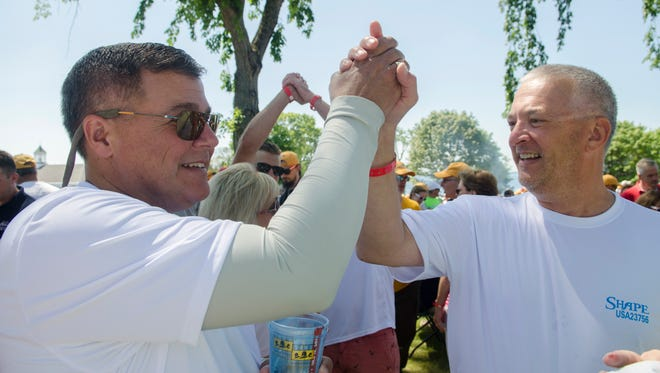 Chris Benedict and Win Cooper III, owners of Shape, give each other a high five as they talk about their race and first place finish Tuesday, July 19, 2016 during the Port Huron-to-Mackinac Island Sailboat Race awards party at Mackinac Island. Shape has won four straight first place finishes in the past four years.