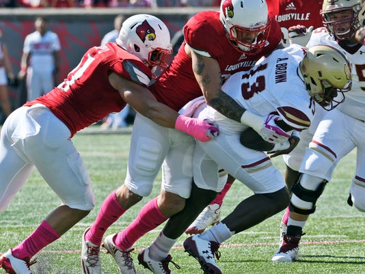Boston College quarterback Anthony Brown (13) is hit by Louisville linebacker James Hearns (99) and London Iakopo (21) during the first half of an NCAA college football game, Saturday, Oct. 14, 2017, in Louisville, Ky. (AP Photo/Timothy D. Easley)