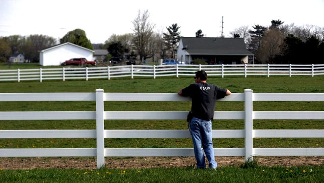 Fairfield Area Humane Society Executive Director Corey Schoonover stands against a fence at the Home of Joy Farm in Pleasant Township. Two horses the Humane Society seized last year are being kept at the farm.