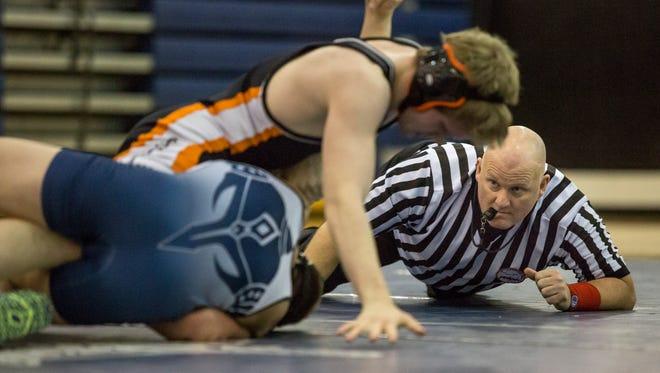 Official Kenneth Nicholl watches closely Marysville's Derek White attempts to pin Armada's Brennen Steinbauer during a wrestling meet Wednesday, Feb. 10, 2016 at Marysville High School.