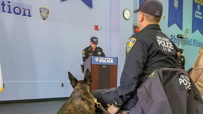 Port Authority Police Officer Heriberto Torres and his K-9, Donna, at Friday morning's graduation ceremony. Sgt. Thomas Hering, the canine training supervisor, speaks at the podium.