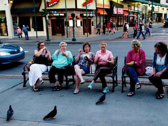 People eat ice cream on a bench on the Parkway in Gatlinburg,