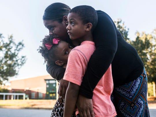 Jemeka Wiley of Anderson hugs her children Angel Hogan,