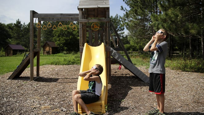 Jack and Raymond Needham, both 9, of New York City, watch the solar eclipse from a play area at Gordon Bubolz Nature Preserve with their grandparents Ellen and Todd Needham, of Fox Crossing, Monday in Grand Chute.