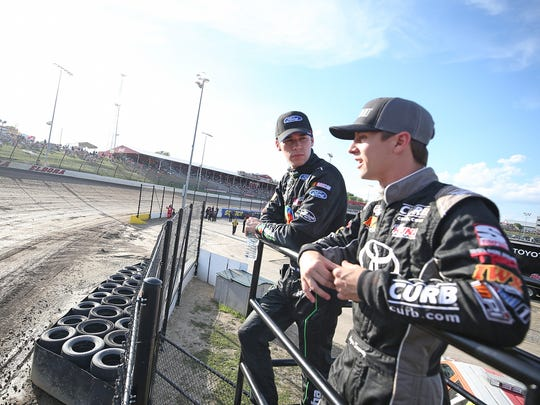 Ben Rhodes, driver of the #41 The Carolina Nut Co. Ford, and Logan Seavey, driver of the #51 Mobil 1 Toyota, watch practice for the NASCAR Camping World Truck Series Eldora Dirt Derby at Eldora Speedway on July 17, 2018 in Rossburg, Ohio.