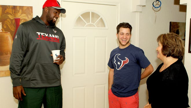 Houston Texans defensive tackle Joel Heath, left, shares a light moment with Conner Gelinas and Conner's mother, Dale-Ann, during a birthday party at the Gelinases' home in Houston on Tuesday, Sept. 20, 2016.  Gelinas, 20, has befriended Heath after being diagnosed with a rare form of sinus cancer.