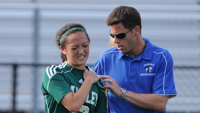 Fairfax (Va.) High School athletic trainer Bret Gustman checks on Langley High School soccer player Courtney Kim after a collision in May 2011. Kim hurt her shoulder but returned to play later in the game.