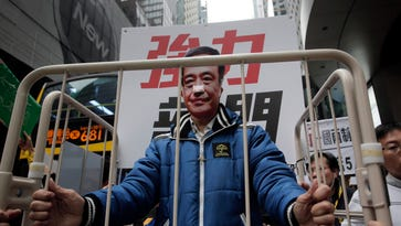 In this Jan. 10, 2016 file photo, a protester wearing a mask of missing bookseller Lee Bo sits in a cage during a protest against the disappearances of booksellers in Hong Kong.
