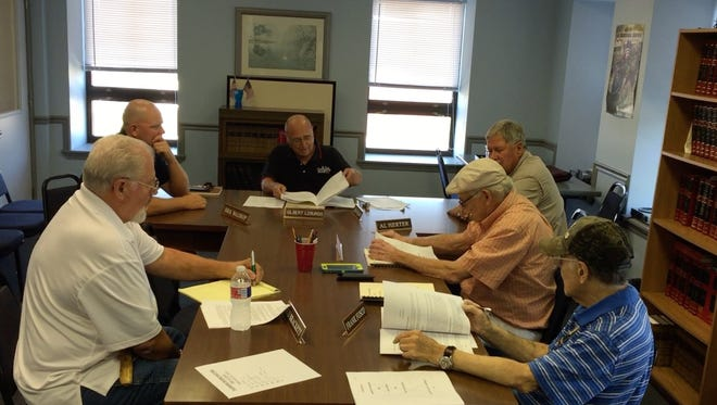Members of the Baxter County Planning Board (clockwise, from left) Rod Brackett, Dirk Waldrop, Gil Losurdo, Al Herter, Don Blair and Frank Fusco discuss the group's final changes to a revised set of county land-develop regulations Tuesday in the third-floor conference room of the Baxter County Courthouse.