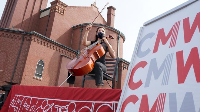 Community Music Works's Adrienne Taylor plays a cello piece on the improvised stage atop a flatbed trailer.