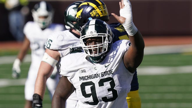 Michigan State defensive tackle Naquan Jones (93) reacts after sacking Michigan quarterback Joe Milton during the second half of an NCAA college football game, Saturday, Oct. 31, 2020, in Ann Arbor, Mich.