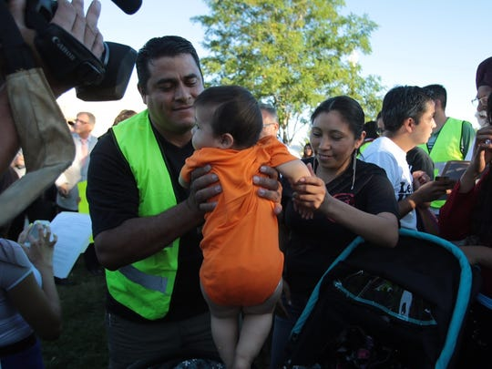 Angel Rosales lifts his son as his wife Elva Rosales looks on. The couple from Guatemala has a 10'year old boy a 7 year old girl are in detention in Texas.