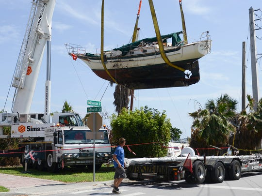 Work crews lift a 37-foot sailboat named Mistress onto a trailer Wednesday afternoon in Cocoa Village. The boat was one of several that were pushed ashore by Hurricane Irma.