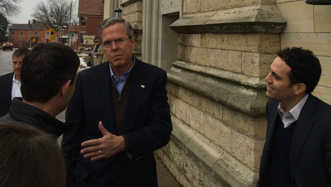 Republican presidential candidate Jeb Bush talks with man outside the Cathedral of St. Raphael in Dubuque on Sunday morning. Bush attended mass at the church on the final day before Iowa caucuses.