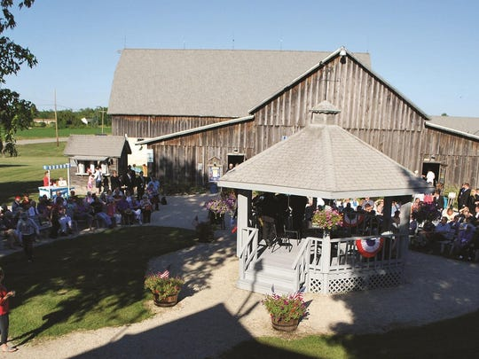 An audience gathers around the gazebo at Birch Creek Music Performance Center to hear a student concert before the main performance in the Dutton Concert Barn, in background.