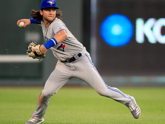 Toronto Blue Jays shortstop Bo Bichette fields a ball in left field hit by Kansas City Royals' Cheslor Cuthbert during the fourth inning of a baseball game at Kauffman Stadium in Kansas City, Mo., Monday, July 29, 2019. Cuthbert doubled on the play. (AP Photo/Orlin Wagner)