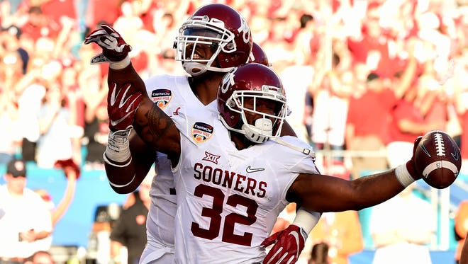 Oklahoma Sooners running back Samaje Perine (32) reacts with offensive tackle Orlando Brown (78) after scoring a touchdown against the Clemson Tigers in the first quarter of the 2015 CFP Semifinal at the Orange Bowl at Sun Life Stadium.