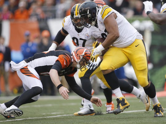 Andy Dalton tackles Steelers defensive end Stephon Tuitt after Tuitt intercepted a pass in the first quarter of their game on Dec. 13, 2015. Dalton left the game with an injury on this play.