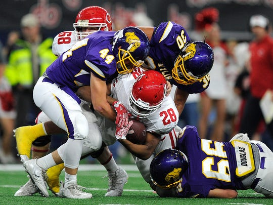 Wylie defenders Josh Goodnature (44), Anthony Guerrero (30) and Trey Hooker (66) tackle Carthage running back Keaontay Ingram (28) during the second quarter of Wylie's 31-17 loss in the Class 4A Div. I state championship game on Friday, Dec. 16, 2016, at AT&T Stadium in Arlington.