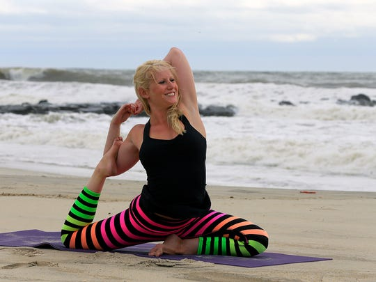 Mandy Unanski Enright, owner of Nutrition Nuptials, a business that focuses on helping couples live healthier lives, practices yoga on the beach in Spring Lake.
