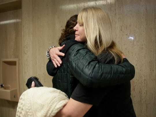 Glass artist Allison Key, 33, of Urban Pheasant Glass, and a tenant at the Russell Center, left, gets a hug from friend Carol Hofgartner, executive director of Art Road, after the City of Detroit Buildings, Safety Engineering and Environmental Department Administration voted to allow occupants to remain at the Russell Center.