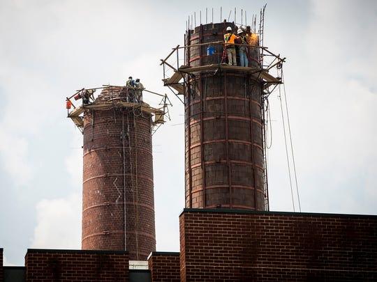 A construction crew dismantles two smokestacks on Ball