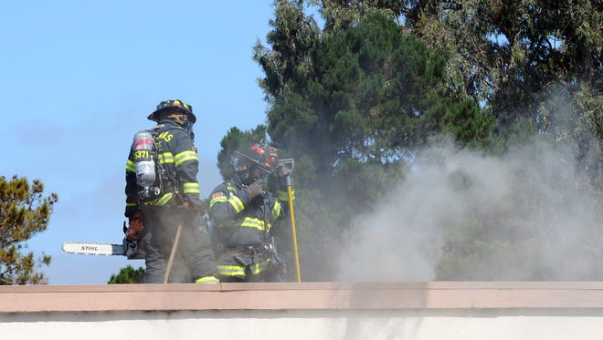 Firefighters on the roof of 918 Acosta Plaza work to contain the remnants of a fire on Monday in Salinas. No one was injured, according to witnesses at the scene.
