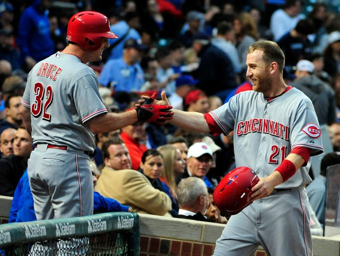 Cincinnati Reds third baseman Todd Frazier (21) is greeted by right fielder Jay Bruce (32)  after scoring against the Chicago Cubs during the sixth inning at Wrigley Field.