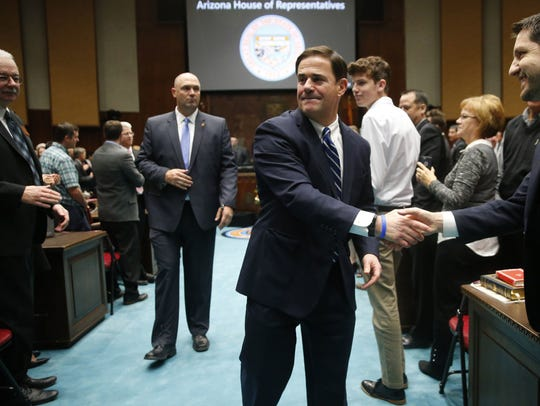 Arizona Gov. Doug Ducey shakes hands in the House of