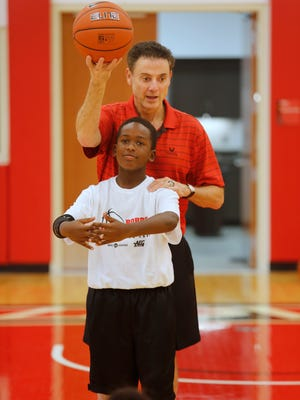 University of Louisville basketball coach Rick Pitino spoke to participants in the Robbie Valentine basketball camp today.  During his talk he used Demetrius Dunlap, age 10, as a basket to demonstrate how putting the proper arc on the ball. July 28, 2015.
