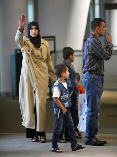 Ahalem Alswedan waves as she spots friendly faces at Louisville International Airport while her husband Ahmad Al Tybawi and sons search in another direction. The family are Syrian refugees and had just arrived in their new city. Sept. 29, 2015.