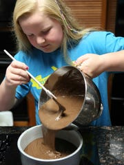 Livvy Feinn, 11, mixes ingredients for cupcakes in the kitchen at her home.