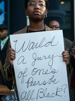 Protestor Shalonte Branham shows her support for Jefferson Circuit Court Judge Olu Stevens Friday just across from the Hall of Justice building. Nov. 20, 2015