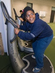 Strive For Success student Andre Johnson tries out one of the Power Plate machines in the Hawkeye football weightroom. Johnson and five other students were given a tour of the Hawkeyes' football facility Friday, December 18 2015.