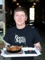 Gospel Bird chef Eric Morris holds the Cheat Day dish at his restaurant in downtown New Albany. The dish consist of frites, country ham, caramelized onions, blue cheese, and fried chicken livers