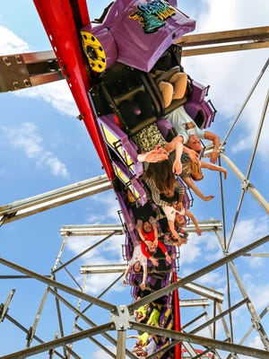 Kentucky Kingdom staff members tride on the theme park's new roller coaster Storm Chaser. The new coaster starts off with a 100-foot corkscrew drop before heading through a series of up-and-downs, sideways turns and further twists.