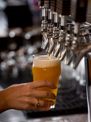 A bartender pours a beer from the tap at Titletown Roof Tap, part of Titletown Brewing Co. in Green Bay.