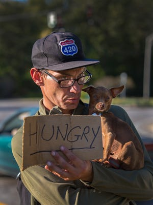 """Mark Rahley talked to his dog """"Nibbles,"""" while panhandling for money at the exit of Interstate 64 at Grinstead Drive. Nibbles is a service dog that can detect when Rahley is about to have a seizure.  The Kentucky Supreme Court will hear free speech arguments Friday on Lexington panhandling ordinance. Rahley says, """"What's the difference between what I'm doing and the guy (farther down Grinstead) with the Hillary Clinton sign?"""""""